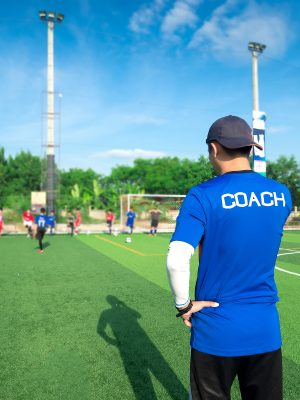 man wearing shirt that says coach on sidelines of a youth soccer game
