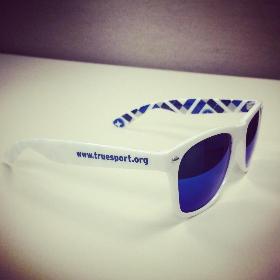 TrueSport branded white sunglasses with blue lenses.