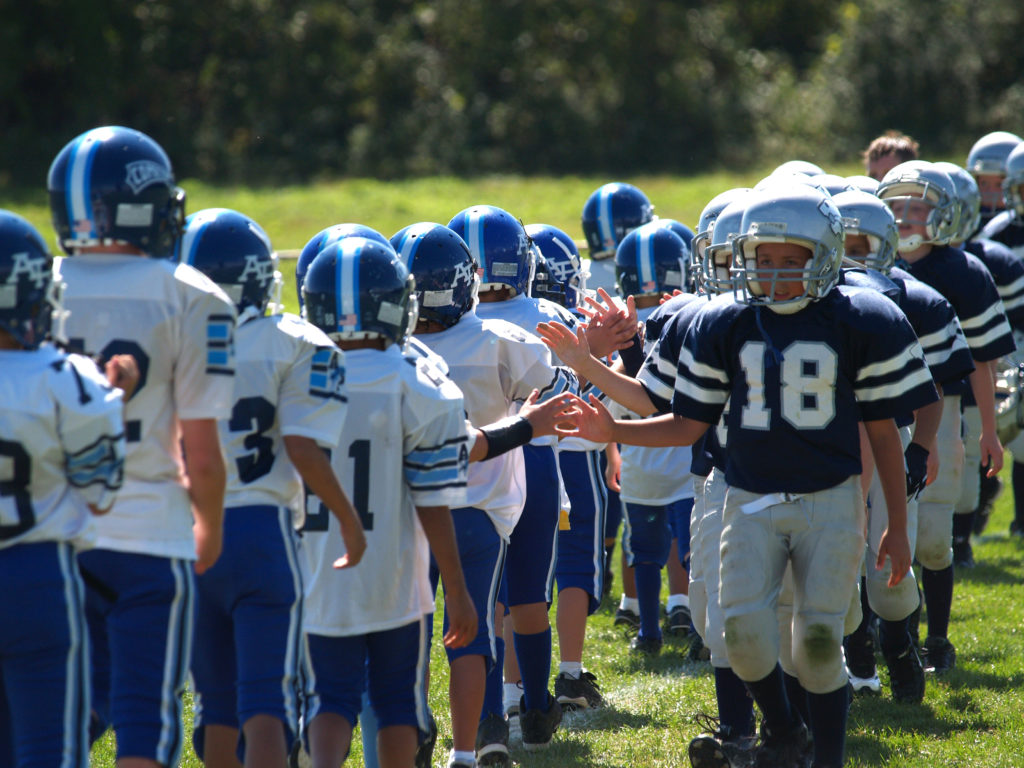 Young football players shaking hands at the end of a game.