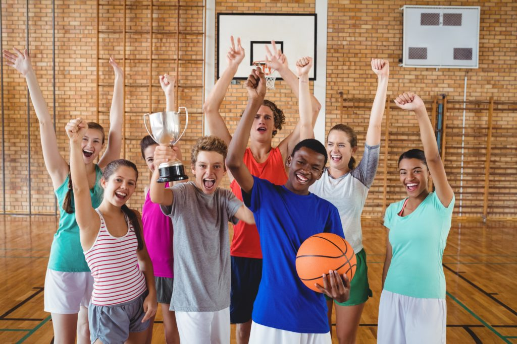 Group of diverse kids cheering while holding a basketball and trophy.