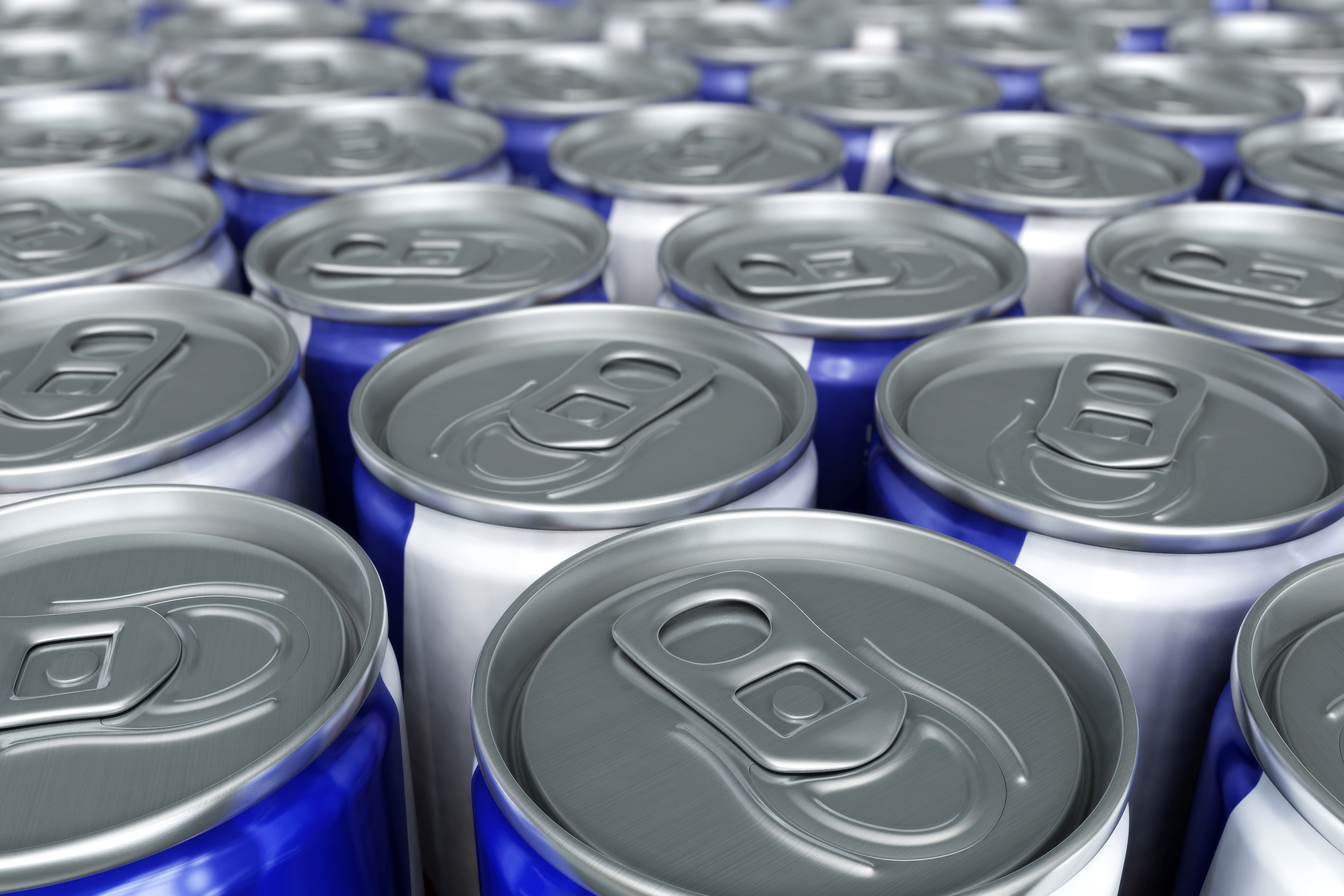 Top view of many cans of energy drinks on a table together.