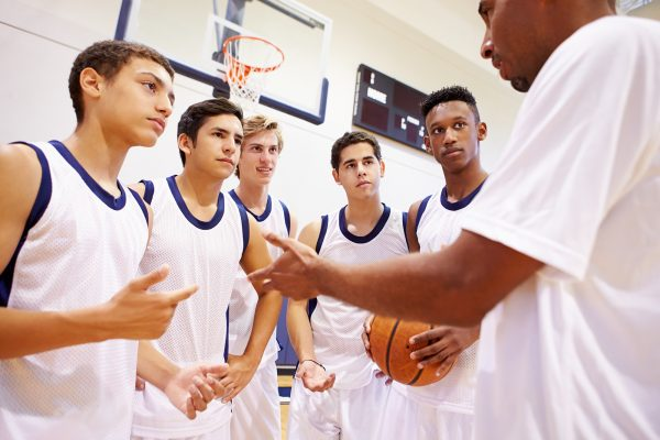 Male coach talking to young male basketball team.